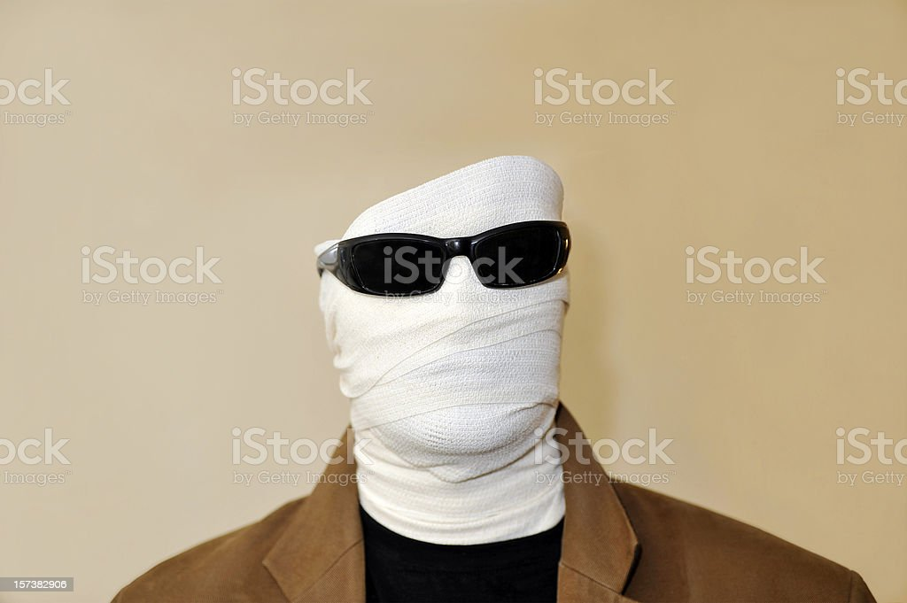 Invisible man with white bandaged face and sunglasses stock photo