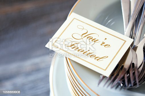 An invitation and a grouping of silverware rest on top of a stack of dinner plates. The image is photographed using a very shallow depth of field.