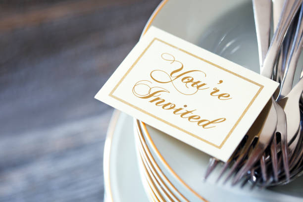 invitation resting on top of stack of dinner plates - приглашение стоковые фото и изображения