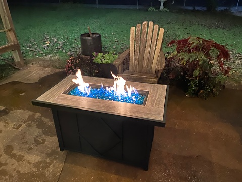 Back porch with wooden chair and roaring gas firepit