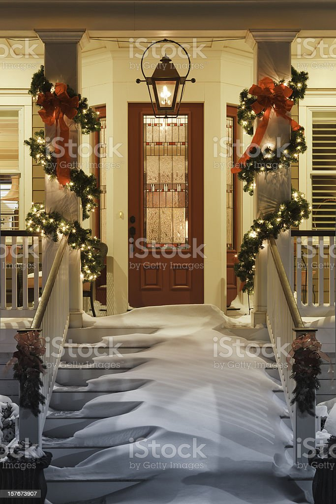inviting Christmas doorway with snow on porch stairs and railing stock photo