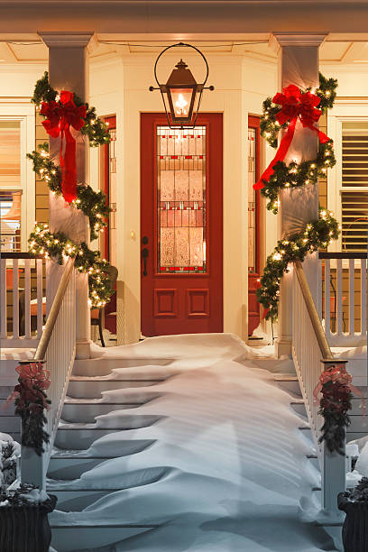 inviting christmas doorway with snow on porch stairs and railing - christmas tree stockfoto's en -beelden