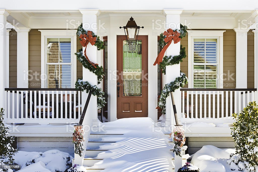 inviting Christmas front doorway with snow on porch stairs stock photo