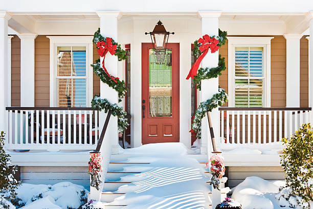inviting christmas front doorway with snow on porch stairs - christmas tree stockfoto's en -beelden