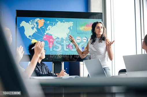A mixed race woman is giving presentation. This confident individual stands in front of a data display monitor, which has colourful world graphics displayed on it. Image focus technique, layers and point of view, help the image to be realistic, as if the viewer is spying on the participants. This lady is a natural leader, she is answering questions from her colleagues. The colour blue is strong in this image.
