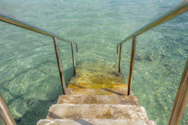 Inviting stairs leading into clear blue ocean water stock photo