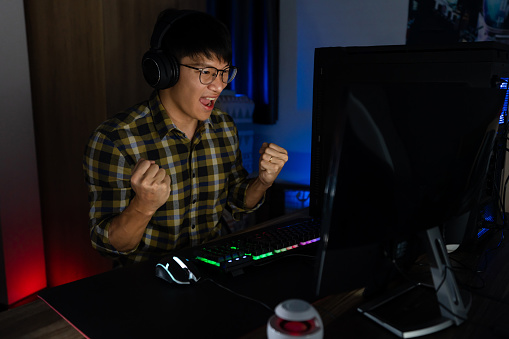 istock Involved asian man cyber sport gamer concentrated playing video games on computer at night dark room at home, eSport and technology concept. 1249504234
