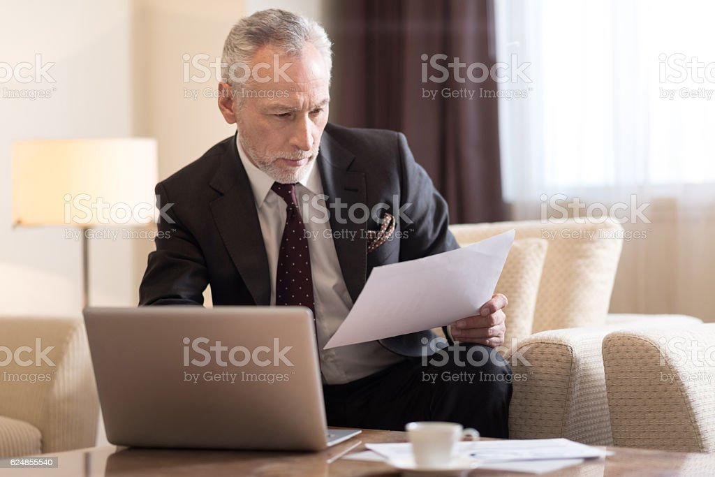 Involved businessman working with papers and sitting in the hotel stock photo