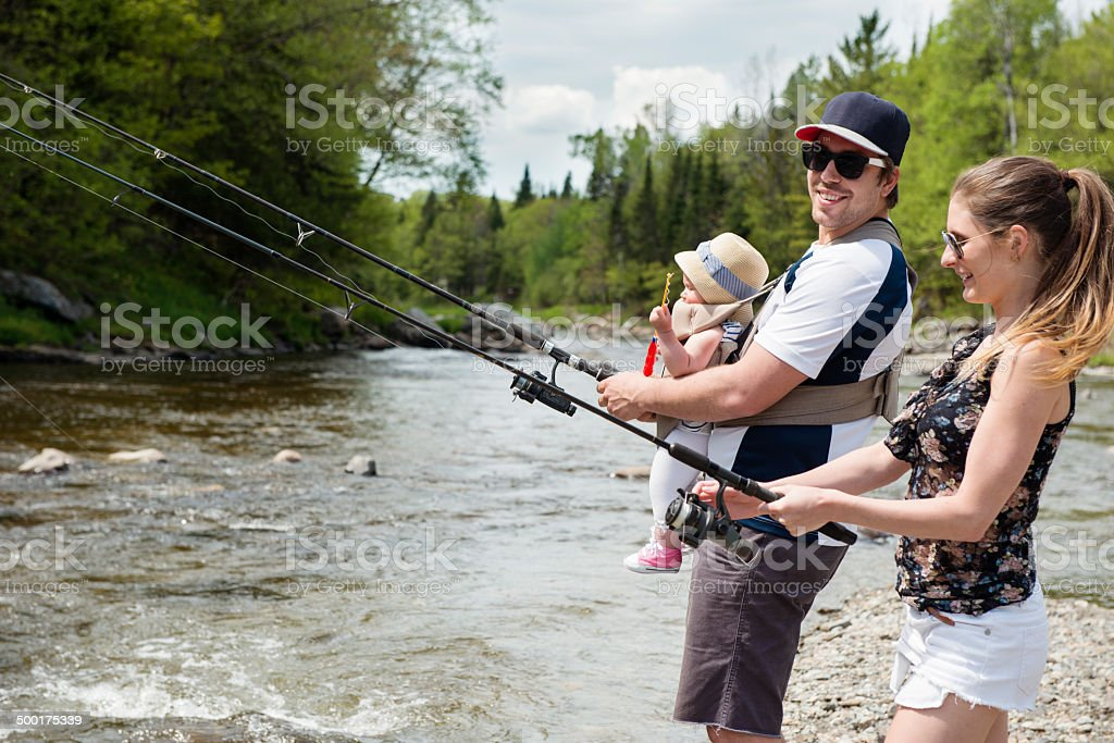 Involved dad and mom with their baby fishing sunny day royalty-free stock photo
