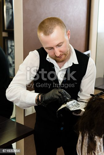 istock involved hairstylist dying a girl's hair with a brush 674930554