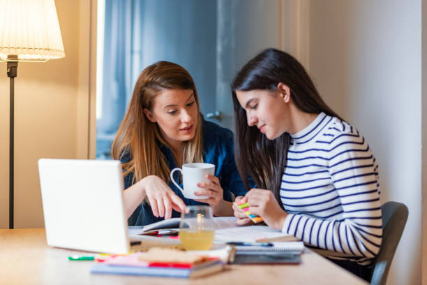 Involved in her daughter's education Photo of young brown hair Caucasian mother is helping her teen  daughter with her homework in front of lap top. They are looking away from the camera. Dark hair schoolgirl and mother together doing homework in home. Beautiful girl and her young mother reading a book together or studying at home during the day. parent stock pictures, royalty-free photos & images