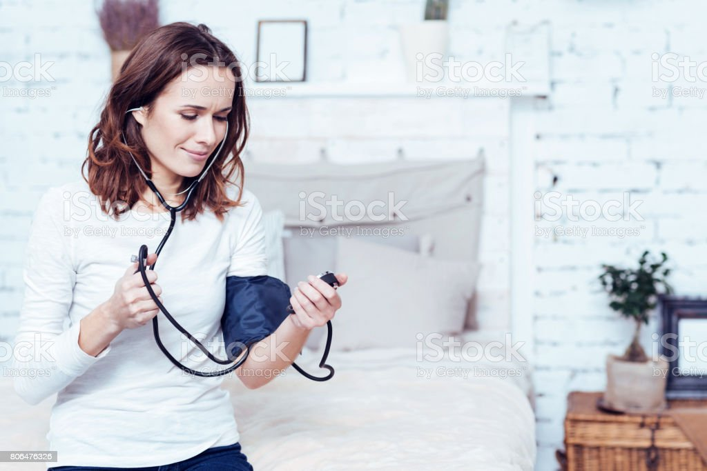 Involved young woman using tonometer at home stock photo