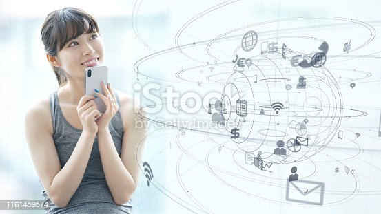 istock IoT (Internet of Things) concept. Asian girl using a smart phone. 1161459574