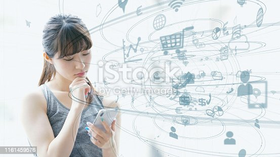 istock IoT (Internet of Things) concept. Asian girl using a smart phone. 1161459576