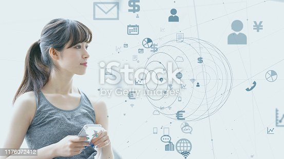 istock IoT (Internet of Things) concept. Asian girl using a smart phone. 1176072412