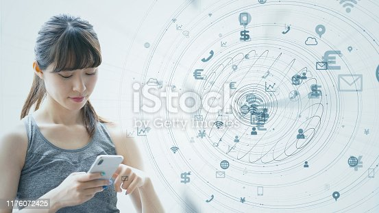 istock IoT (Internet of Things) concept. Asian girl using a smart phone. 1176072425
