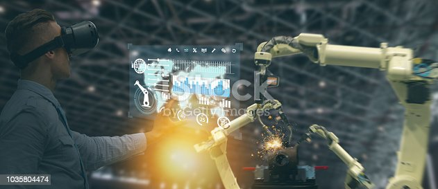 istock iot industry 4.0 concept,industrial engineer(blurred) using smart glasses with augmented mixed with virtual reality technology to monitoring machine in real time.Smart factory use Automation robot arm 1035804474