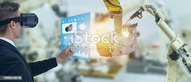 1150202730 istock photo iot industry 4.0 concept,industrial engineer using smart glasses with augmented mixed with virtual reality technology to monitoring machine in real time.Smart factory use Automation robot arm 1066949546