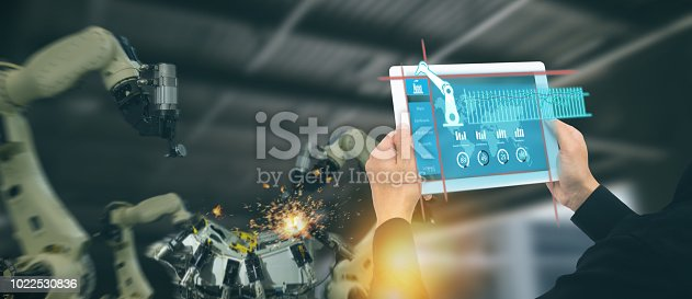 istock iot industry 4.0 concept,industrial engineer using software (augmented, virtual reality) in tablet to monitoring machine in real time.Smart factory use Automation robot arm in automotive manufacturing 1022530836