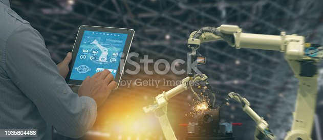 istock iot industry 4.0 concept,industrial engineer using software (augmented, virtual reality) in tablet to monitoring machine in real time.Smart factory use Automation robot arm in automotive manufacturing 1035804466