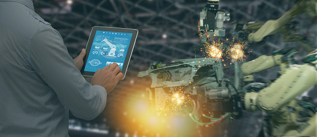 istock iot industry 4.0 concept,industrial engineer using software (augmented, virtual reality) in tablet to monitoring machine in real time.Smart factory use Automation robot arm in automotive manufacturing 1037886276