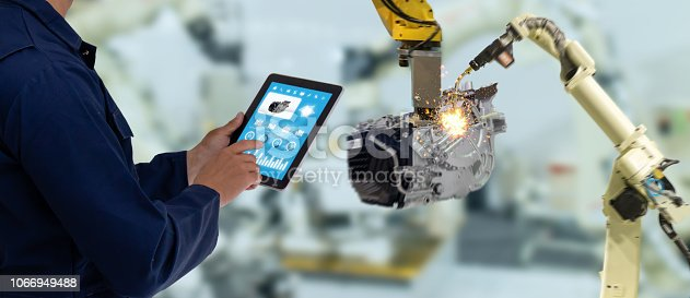 1142508104 istock photo iot industry 4.0 concept,industrial engineer using software (augmented, virtual reality) in tablet to monitoring machine in real time.Smart factory use Automation robot arm in automotive manufacturing 1066949488