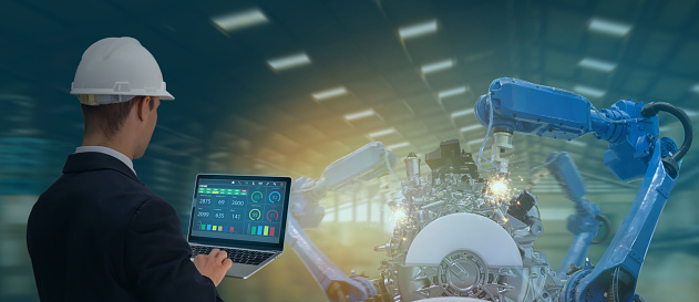 istock iot industry 4.0 concept,industrial engineer using software (augmented, virtual reality) in tablet to monitoring machine in real time.Smart factory use Automation robot arm in automotive manufacturing 1154387323