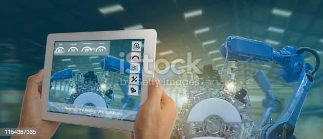 istock iot industry 4.0 concept,industrial engineer using software (augmented, virtual reality) in tablet to monitoring machine in real time.Smart factory use Automation robot arm in automotive manufacturing 1154387335