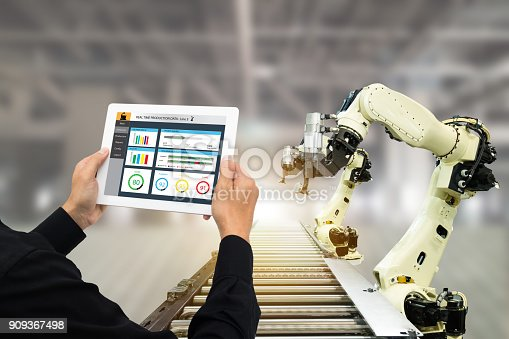 istock iot industry 4.0 concept,industrial engineer using software (augmented, virtual reality) in tablet to monitoring machine in real time.Smart factory use Automation robot arm in automotive manufacturing 909367498