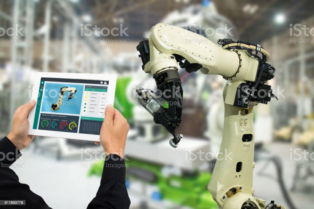 iot industry 4.0 concept,industrial engineer using software (augmented, virtual reality) in tablet to monitoring machine in real time.Smart factory use Automation robot arm in automotive manufacturing foto stock royalty-free