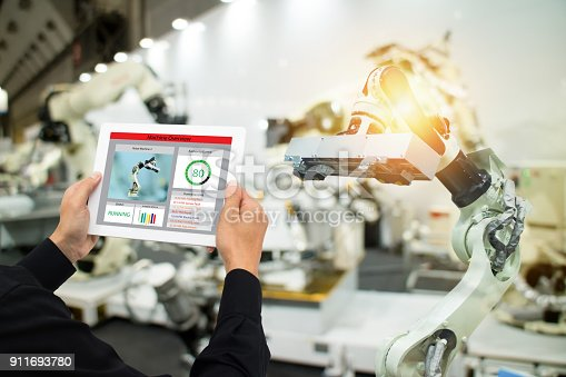istock iot industry 4.0 concept,industrial engineer using software (augmented, virtual reality) in tablet to monitoring machine in real time.Smart factory use Automation robot arm in automotive manufacturing 911693780