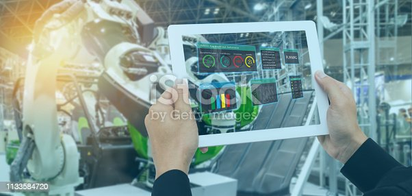 1022530836 istock photo iot industry 4.0 concept,industrial engineer(blurred) using tablet with augmented mixed with virtual reality technology to monitoring machine in real time.Smart factory use Automation robot arm 1133584720