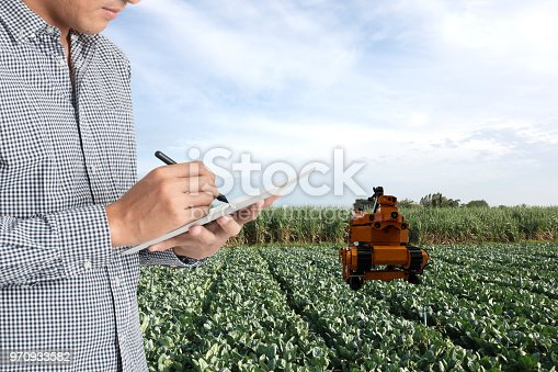 istock iot, smart agriculture in the futuristic concept, smart farmer use robot in agriculture to keep ,collect vegetable, fruit, product in the farm and use tablet keep data, analysis in the real time 970933582