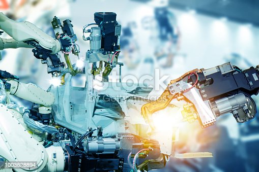 istock iot smart factory , industry 4.0 technology concept, robot arm in automation factory background with fake sunlight on operation line, Futuristic in the new trend technology 1003628894