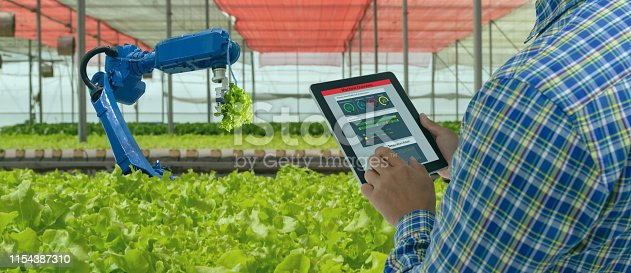 istock iot smart industry robot 4.0 agriculture concept,industrial agronomist,farmer using software Artificial intelligence technology in tablet to monitoring condition and control automatic robotics in farm 1154387310