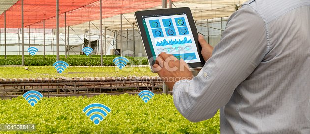 1047941544istockphoto iot smart industry robot 4.0 agriculture concept,industrial agronomist,farmer using tablet to monitor, control the condition in vertical or indoor farm ,the data including Ph, Temp, Ic, humidity, co2 1042088414