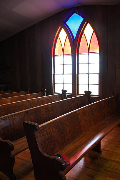Iowa Country Church Stained Glass Window This arched, stained glass window casts a soft glow on the wooden pews in this central Iowa country church.  pew stock pictures, royalty-free photos & images
