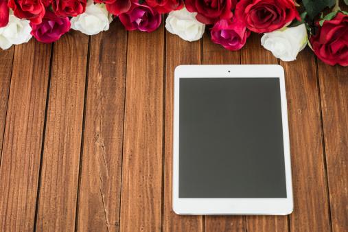 Ipad mini on wood plank table with rose flower