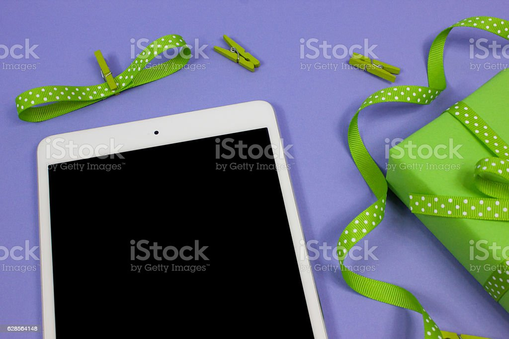 iPad mini with green gift on lilac background stock photo