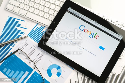 Sydney, Australia – September 6, 2011: Apple IPad on a desk showing the Google home page. There is also a keyboard, glasses and a pen and some documents on the desk, the documents show financial figures with charts and graphs. This scene depicts ipad in a working environment.