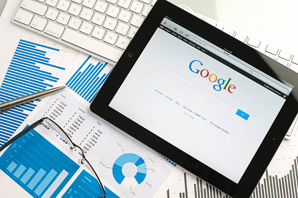 ipad on a desk showing google - search engine stock photos and pictures