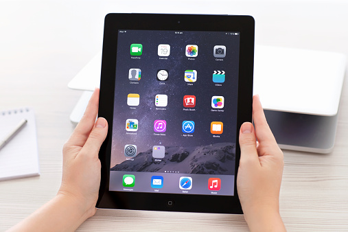 iPad with IOS 8 in hands on background Macbook