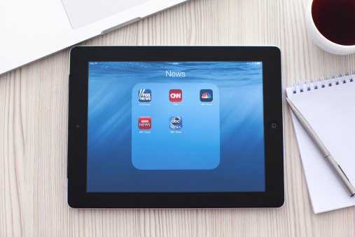 iPad with popular news app on screen the table