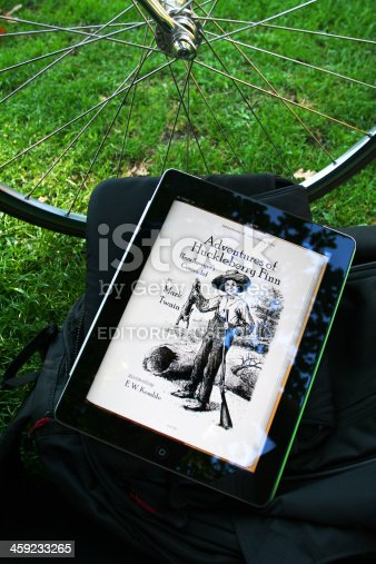 Madrid, Spain - September 9, 2011: Mark Twain\'s Huckleberry Finn in electronic book format on iPad2 in the park
