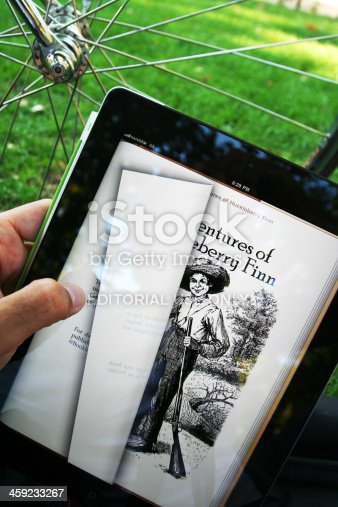 Madrid, Spain - September 9, 2011: Man reading Mark Twain's Huckleberry Finn in electronic book format on iPad2 in the park