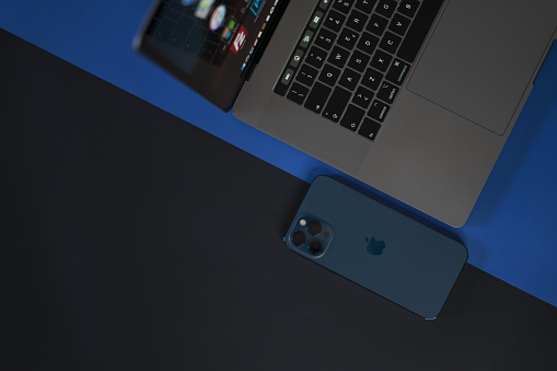 iPhone 12 pro and Macbook Pro on black and blue background