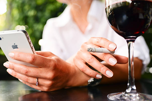iPhone 4s, glass of wine and cigarette in woman hands stock photo