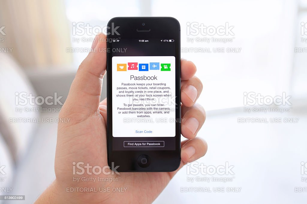 iPhone 5 in male hand with Passbook on the screen stock photo