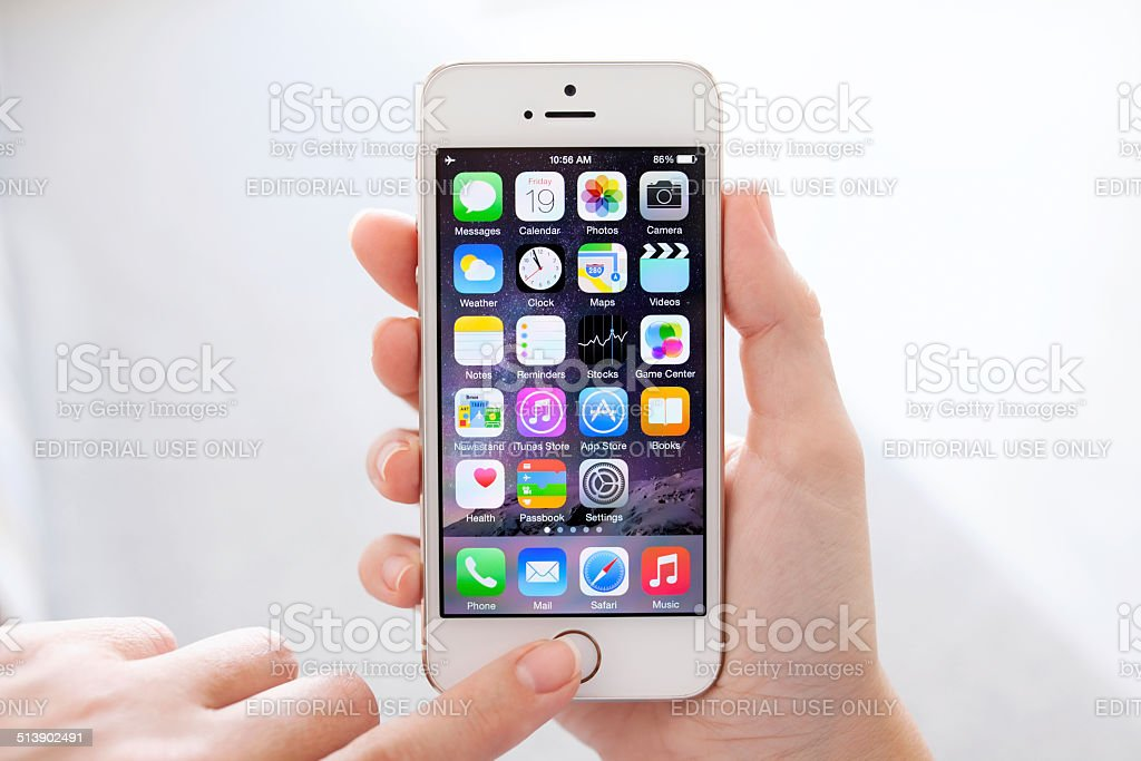 iPhone 5S Gold with IOS 8 in female hands stock photo