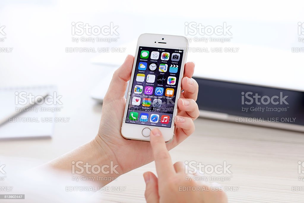 iPhone 5S with IOS 8 in hand on background MacBook stock photo